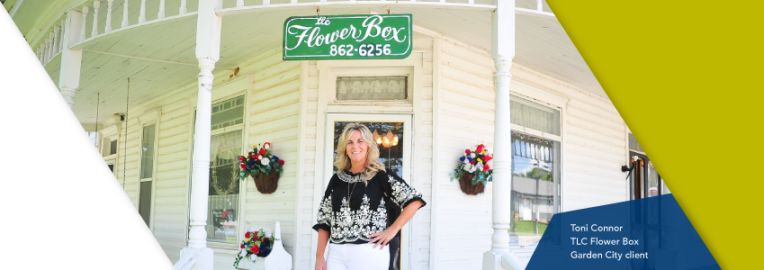 The owner of TLC Flower Box, a Lead Bank Garden City community client, in front of her shop