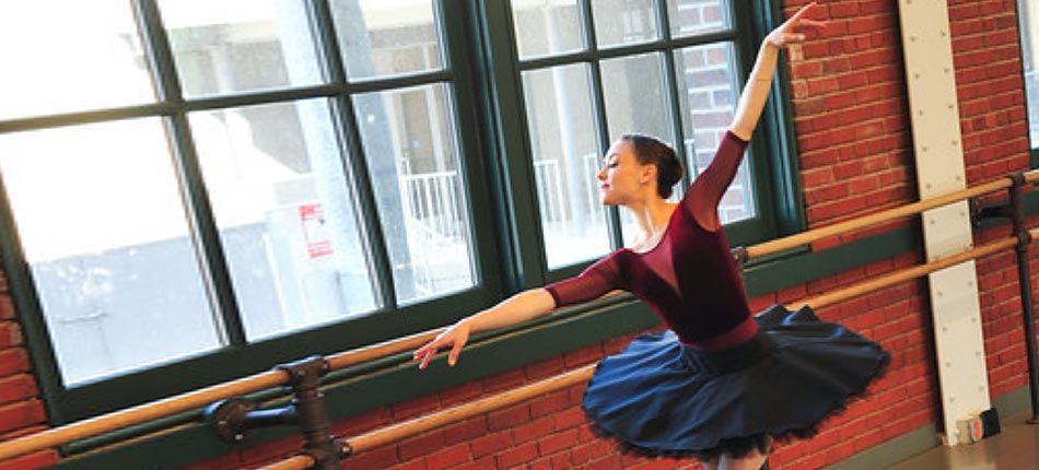A Lead Bank client who is a ballerina stretching by a window