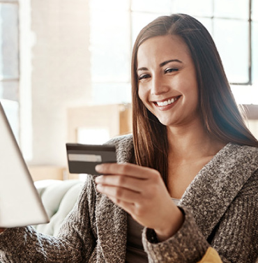 woman holding credit card and tablet